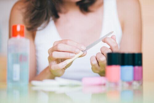 женщина пилит ногти
