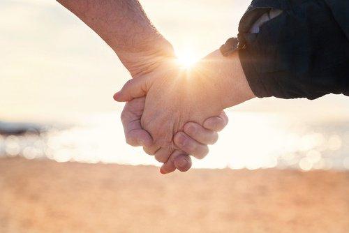 пара у моря держится за руки
