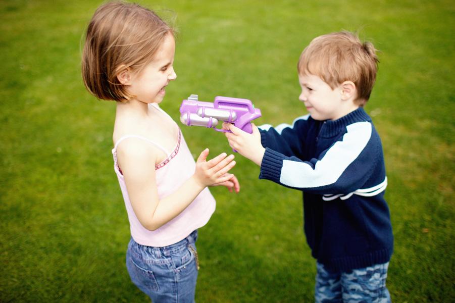 мальчик с пистолетом целится в девочку