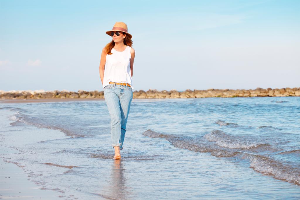 среднего возраста женщина идет по солнечному пляжу