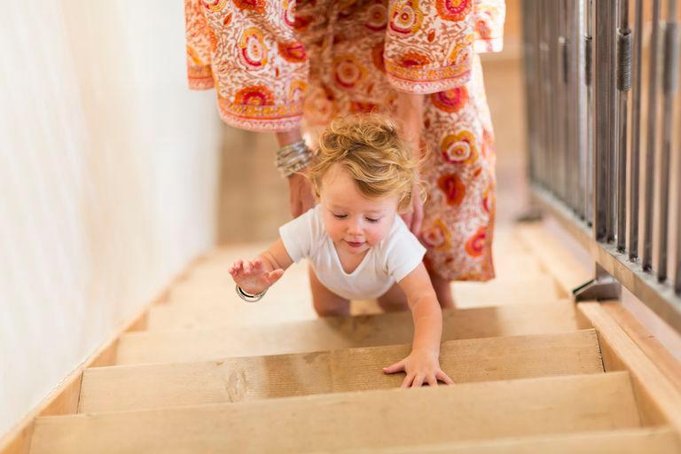 мать помогает ребенку подняться по лестнице