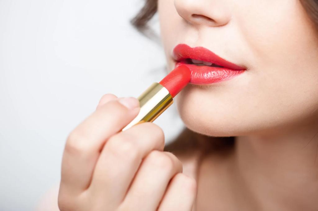 женщина использует губную помаду