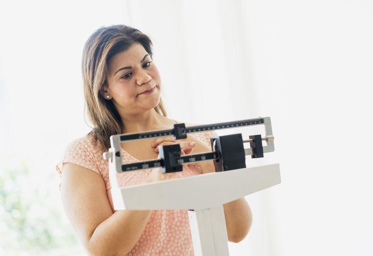 женщина, стоящая по весах