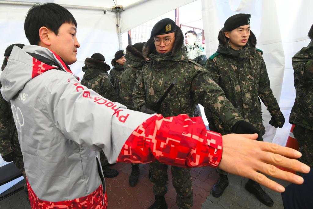 солдаты осматривают посетителя на олимпиаде