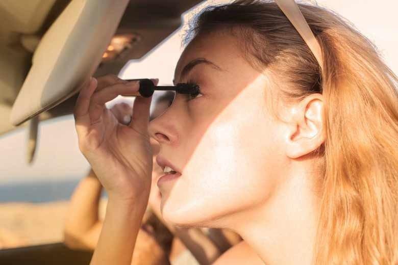 девушка красит глаза в машине