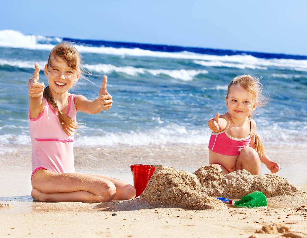 Дети на пляже играют с песком